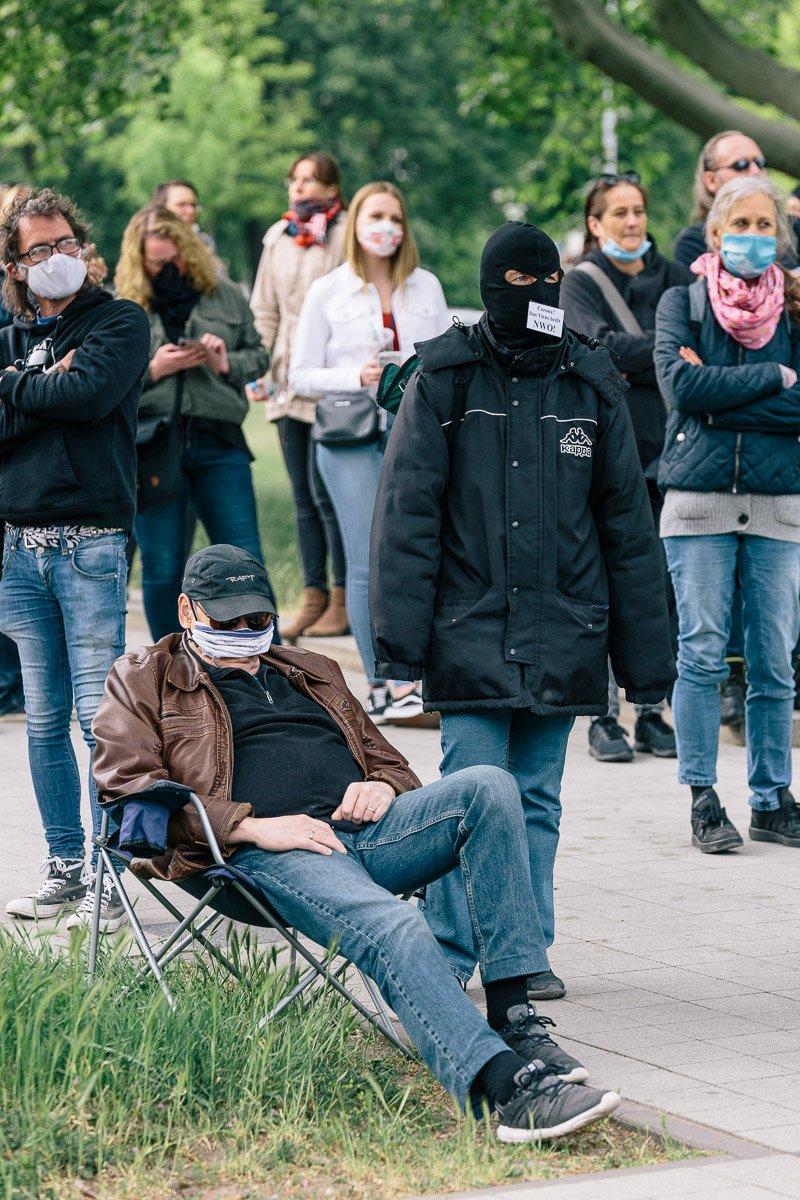 """Maskierte Teilnehmer*innen bei der """"Corona Diktatur nein Danke!"""" Kundgebung am Goseriedeplatz am 16.05.20."""
