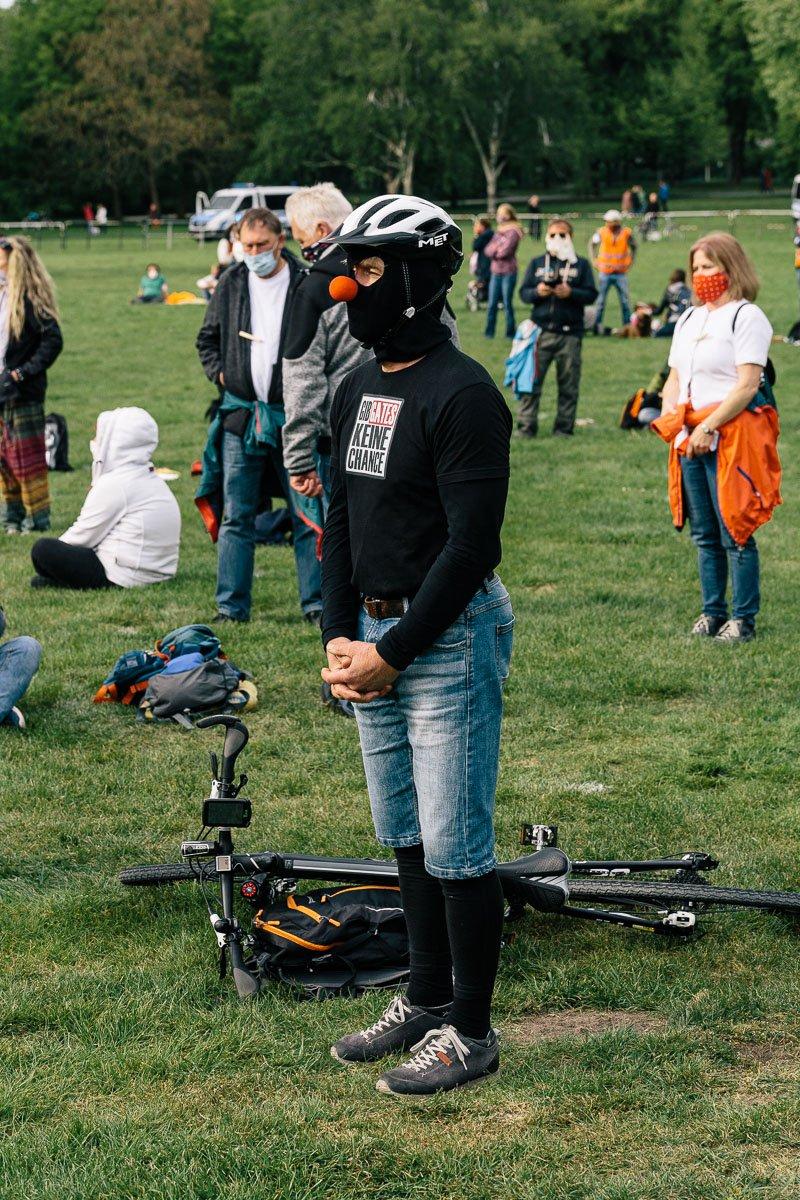 """Ein vermummter Teilnehmer der """"Wir wachen auf"""" Kundgebung im Georgengarten am 16.05.20."""
