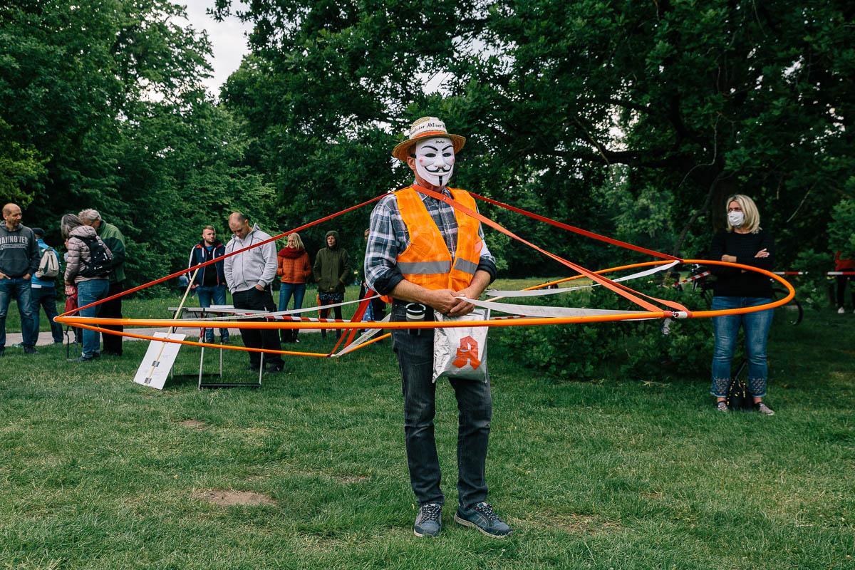"""Ein maskierter Teilnehmer der """"Wir wachen auf"""" Kundgebung im Georgengarten am 16.05.20."""