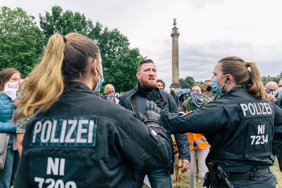 """Die Polizei drängt einen Teilnehmer der """"Wir wachen auf"""" Kundgebung am Waterlooplatz zurück."""