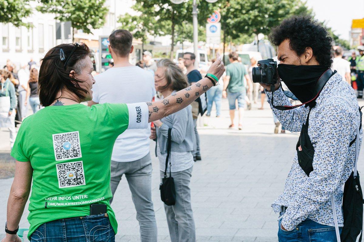 """Eine Teilnehmerin des """"Walk to freedom"""" zeigt einem Pressefotografen den Mittelfinger."""