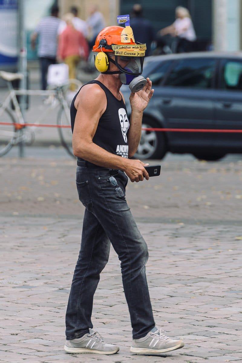 """Ein vermummter Teilnehmer bei der Kundgebung des """"Walk to freedom"""" am 25.07.20."""